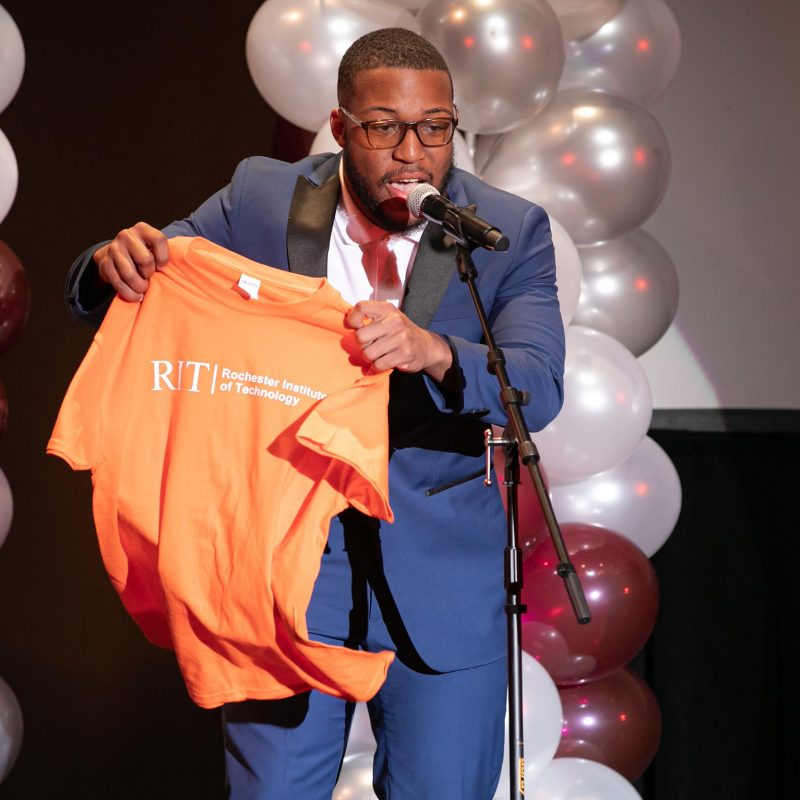 student unfurls a Rochester Institute of Technology shirt during a college signing ceremony